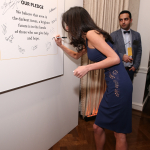 Amal Clooney signing pledge wall