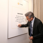 George Clooney signing pledge wall